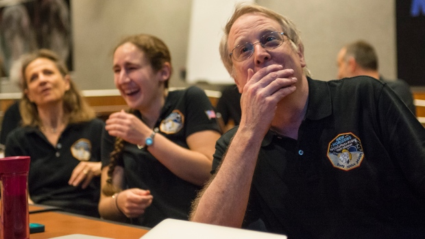 Members of the New Horizons science team react to seeing the spacecraft's last and sharpest image of Pluto. Credit: Bill Ingalls/NASA